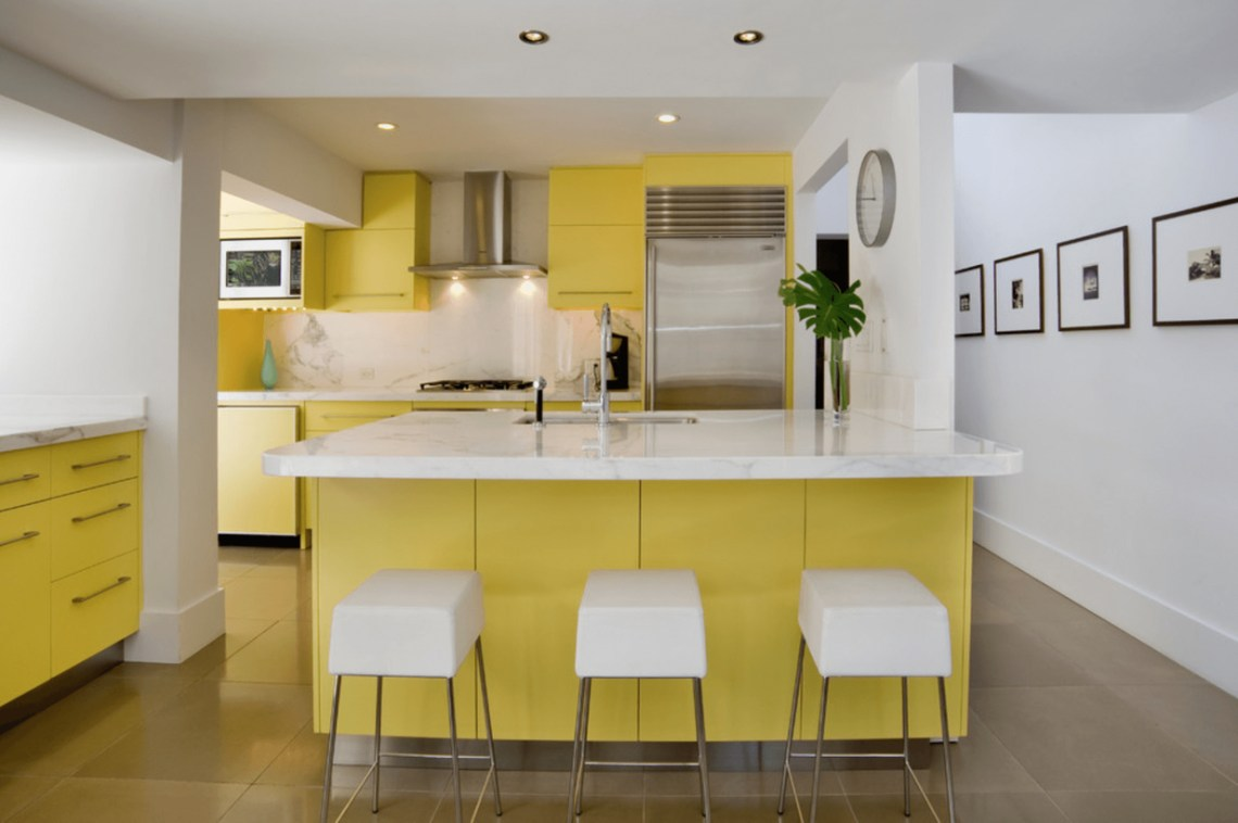 Stunning yellow and white kitchen with yellow cabinet storage, white chairs, white walls, brown floors
