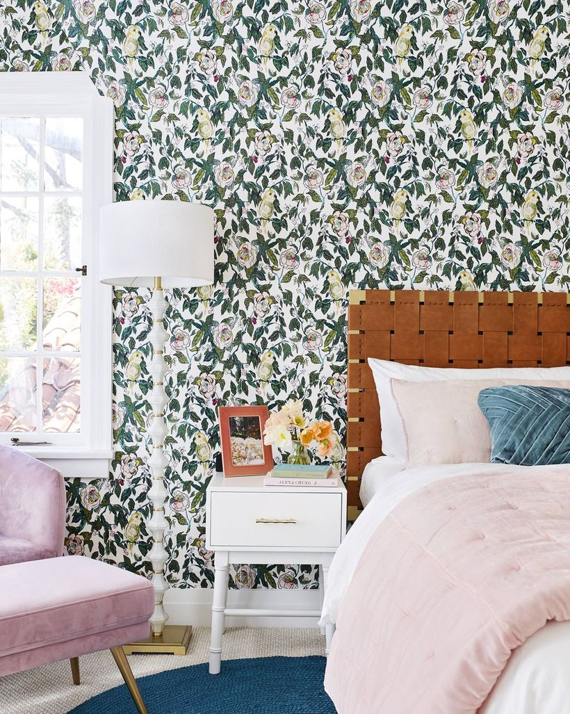 A cozy bedroom design with flower wallpaper, a white window, a white night stand to store house plant, and floor lamp to create good lighting