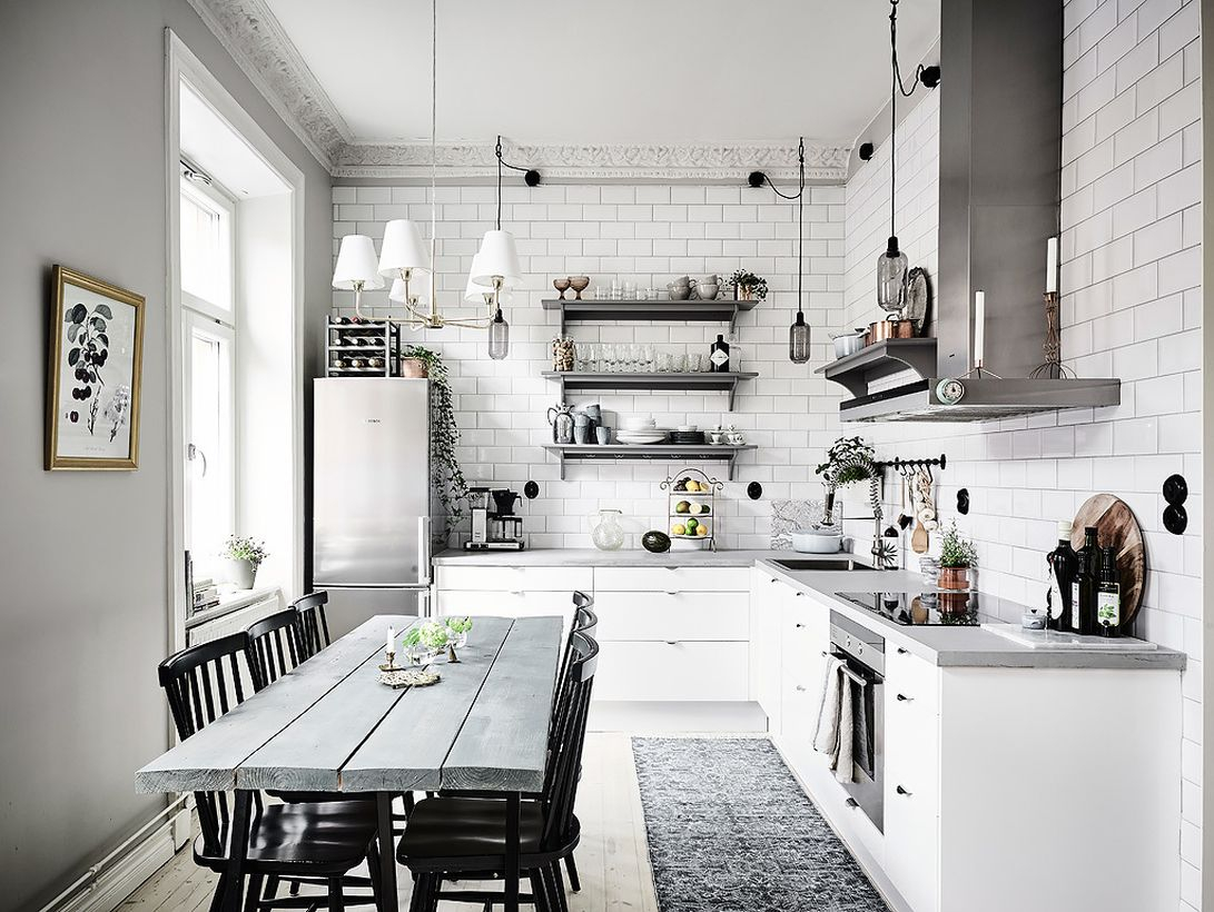 A gorgeous white and grey kitchen design with white brick walls, grey hanging racks to put some kitchen equipment, a grey modern stove, a grey chimney hood cooker, and dining room design