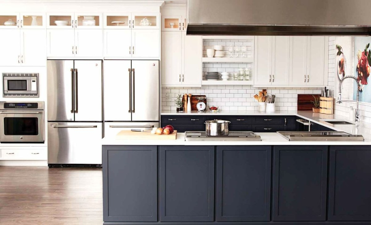 A modern black and white kitchen design with black and white kitchen cabinet storages, white splash pattern brick walls, white hanging rack in the middle of cabinet