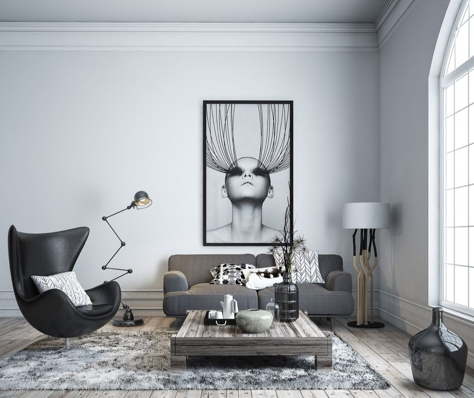 A modern living room monochrome color design with white and grey carpet, big painting on the walls, grey sofa, wooden coffee table, a house plant, a black jars, decorative lighting