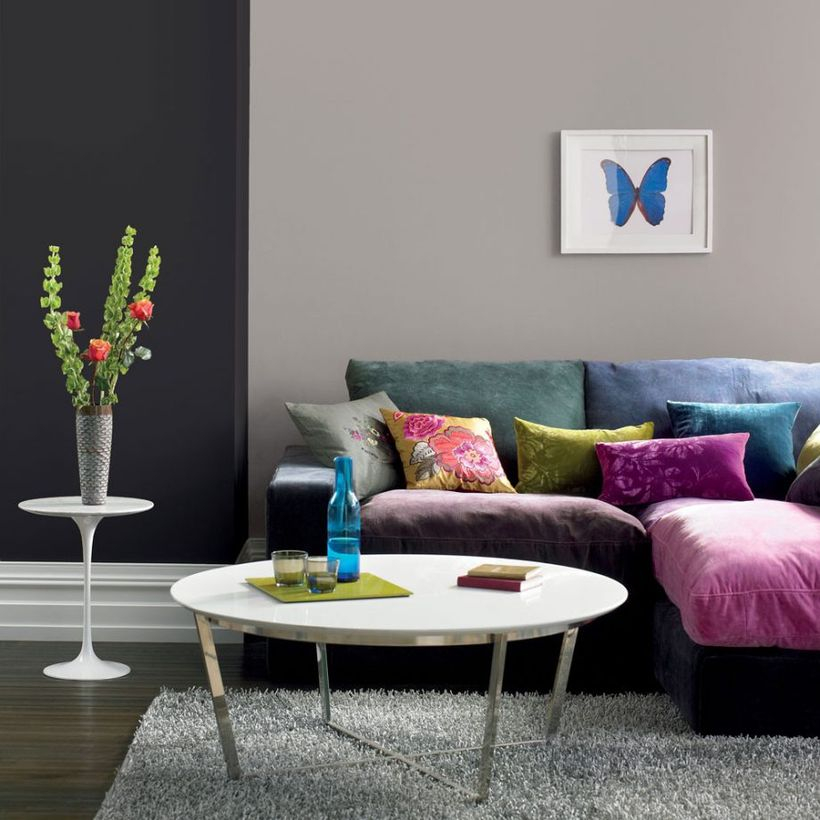 A simple living room grey home design with black and grey walls, soft sofas colorful, a round white coffee table, a white table to put some house plant, and a soft gray carpet