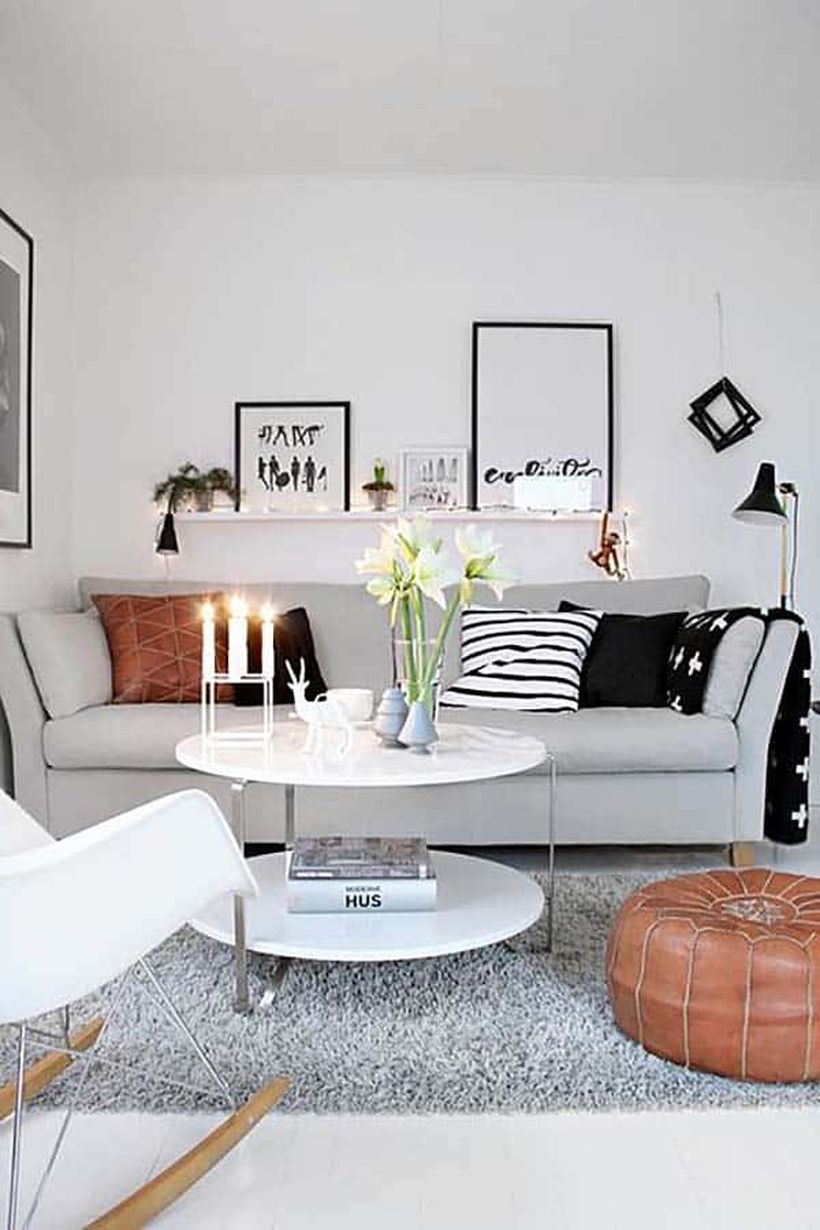 A simple monochrome living room design with white walls, a grey sofas, a white round coffee table, a long hanging rack to place artworks, adn decorative lighting to create good lighting