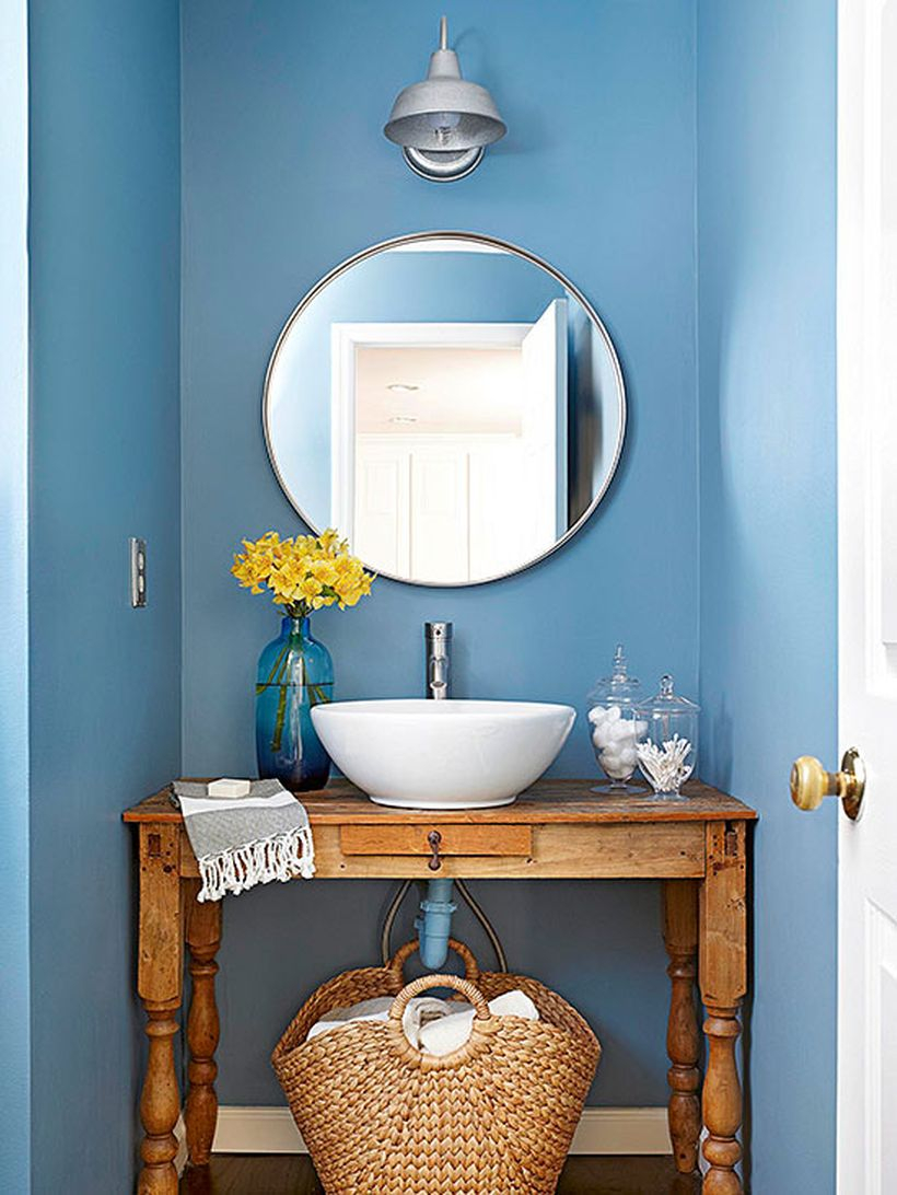 A simple small bathroom decor ideas with blue walls, rustic wooden table for sink, a round mirror, rattan basket to put towels and decorative lighting