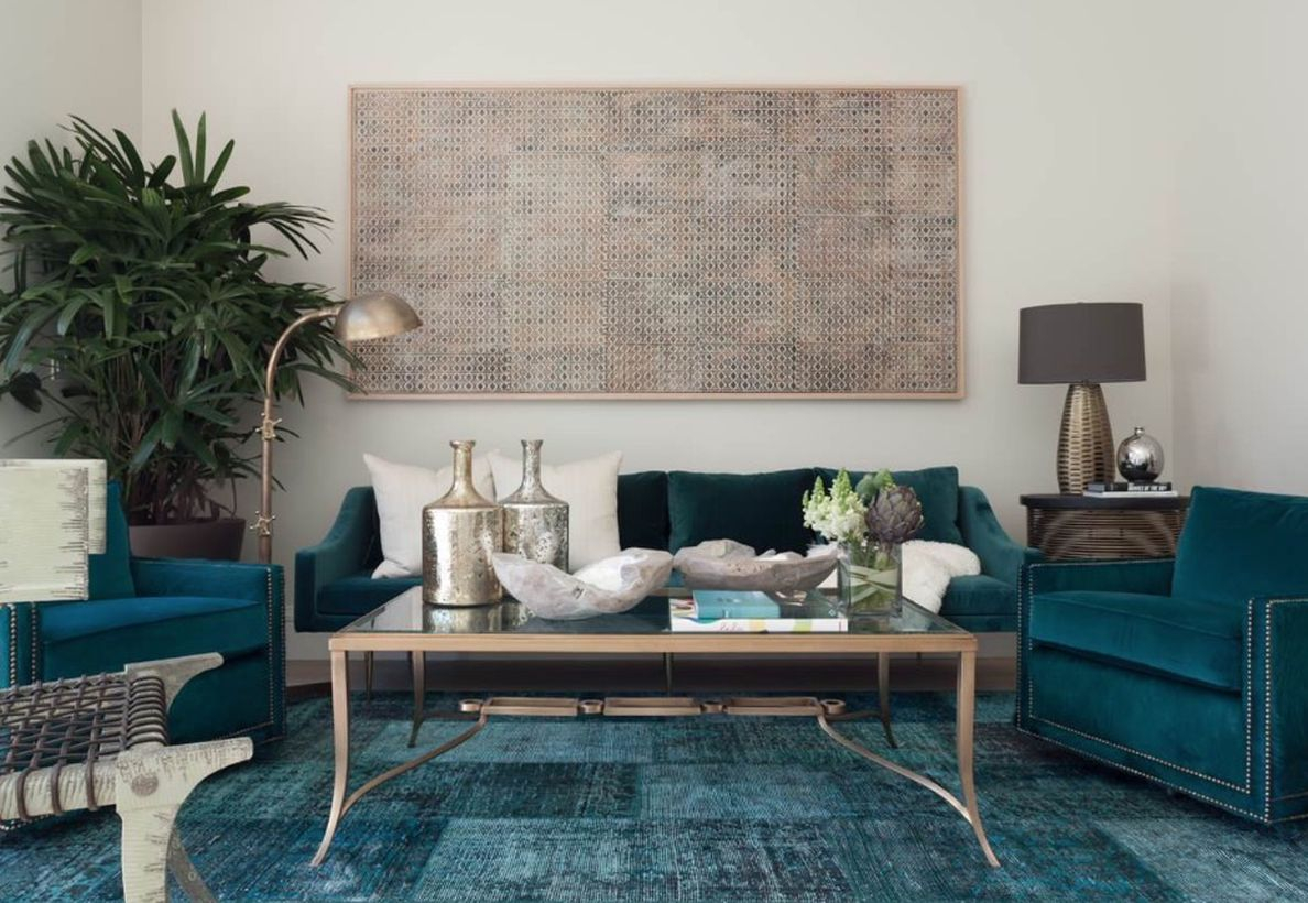 A stunning living room monochrome color design with white walls, black and white sofa cushions, a metal layer coffee table, a house plant at the corner, and table lamp