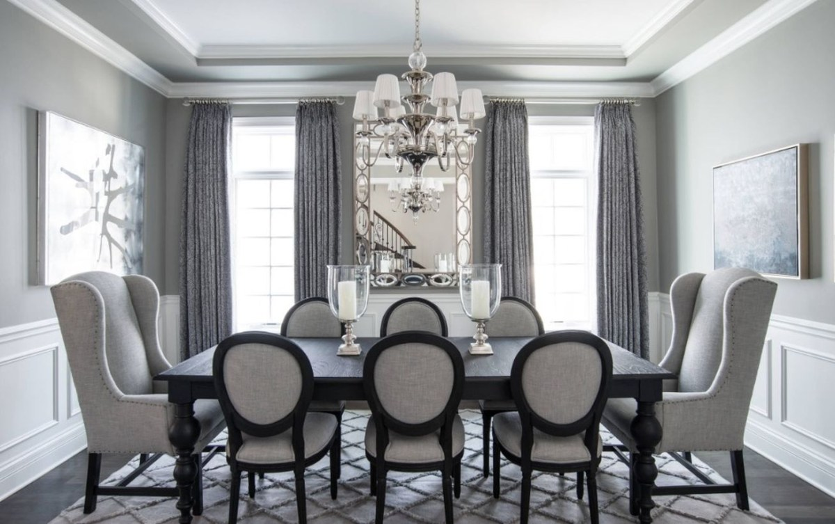 An elegant monochrome color dining room decoration with white and grey walls, gray curtains, hanging decorative lights, black and grey furniture