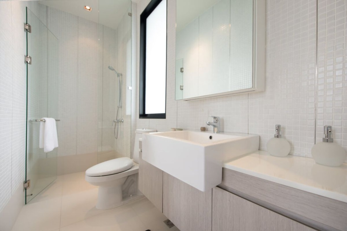 An elegant white bathroom decor ideas with white plaid ceramic walls, a white sink, a towel hook on the glass door, and grey bathroom storage cabinets