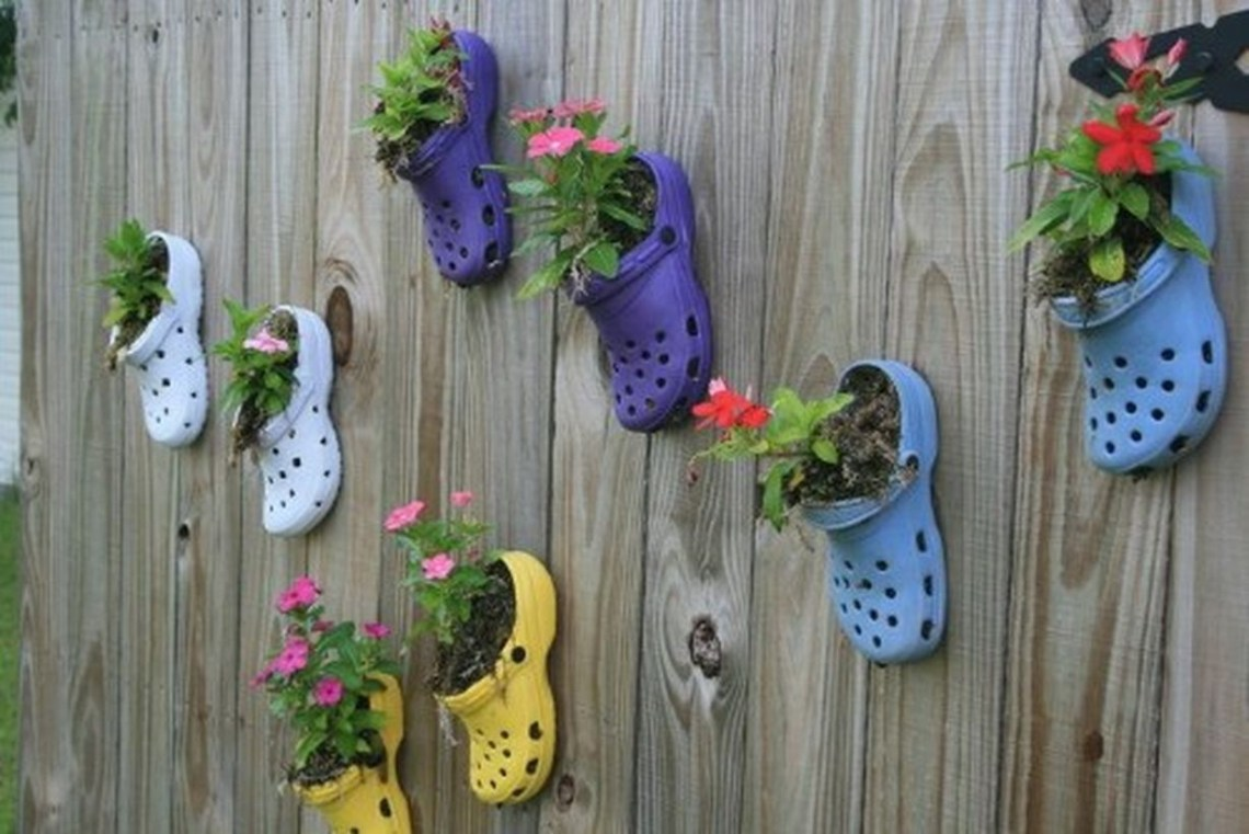 A beautiful plant decoration for garden with those old crocs that you never wear anymore or that the kids have outgrown will make beautiful planters for your fence.