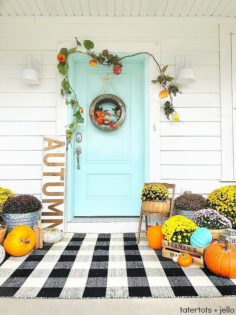 A creative outdoor redecoration from summer to fall with black and white plaid rug, some pumpkins, the rustic galvanized wreath and the overall beautiful color contrast.