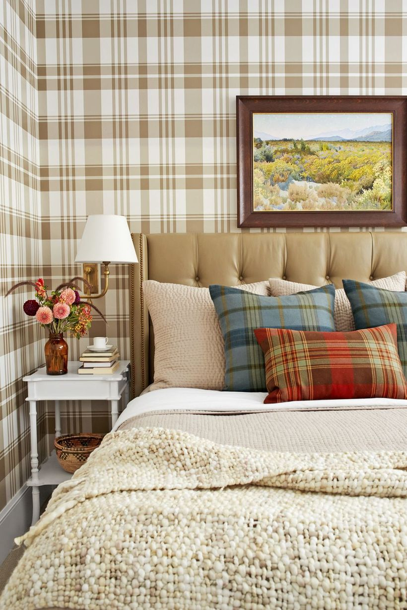 A stunning indoor redecoration from summer to fall with incorporate natural elements and earthy wallpaper. piled plaid pillows, blankets, and a cushy headboard.