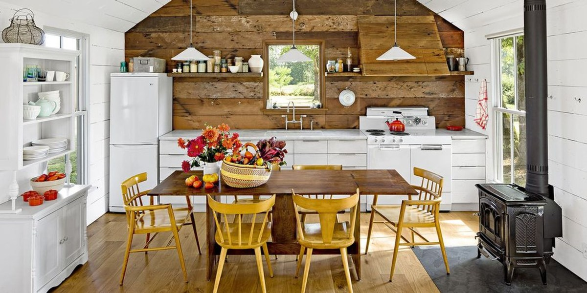 A stylish indoor redecoration from summer to fall with rustic white kitchen, apples, flowers, squash display on the table and golden yellow painted chairs also give this neutral kitchen homey