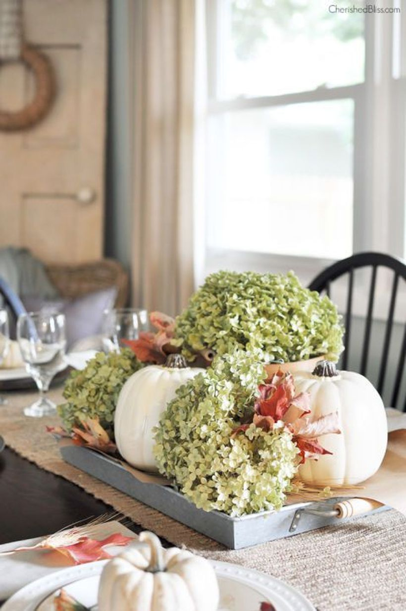 A unique indoor redecoration from summer to fall with white pumpkins, dried hydrangeas, and fallen leaves on a tray to create a portable centerpiece.