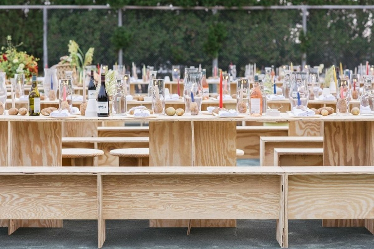 A unique outdoor table set for wedding with long wooden vinyl table, wooden vinyl chairs, glass bottles that will make your wedding look fantastic.