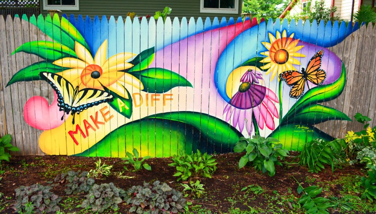 A wonderful painting fence for garden with uplifting colours, pictures, and quotes in the backyard garden.