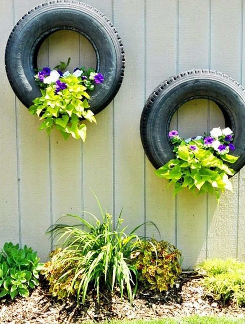 A wonderful plant decoration for fence with recycled tire planters this is a great way to bring it all together the tires hang perfectly on wooden fences.