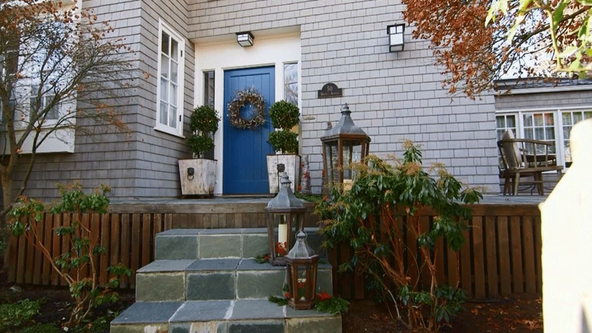 An adorable farmhouse porch ornament with plants in pot square, candle lights, lights on walls and wreaths