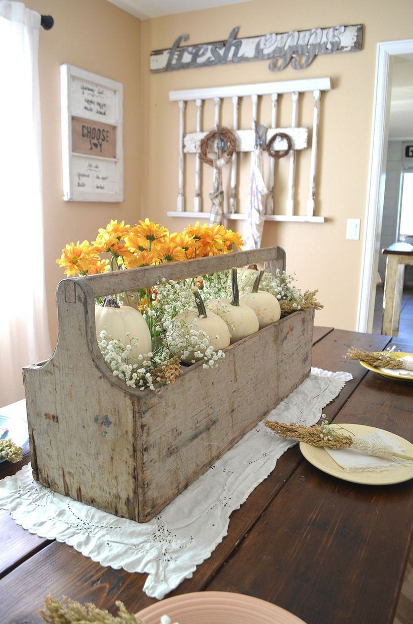 An adorable small white pumpkin ornaments with flowers and square wooden container