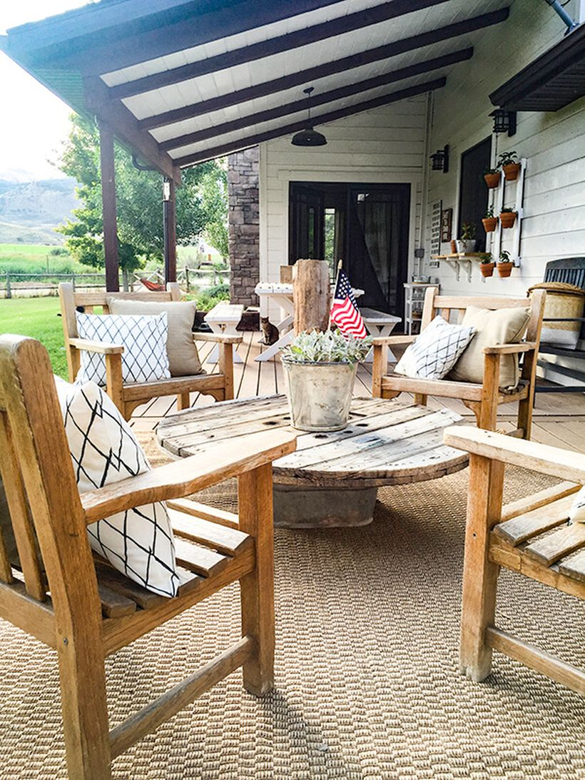 An amazing farmhouse porch furniture with wooden chairs and a round wooden table ideas to complete your front yard
