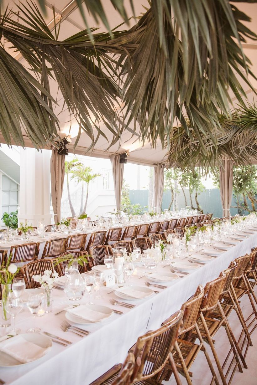 An adorable indoor table set for wedding with long wooden tables, rattan chairs, dried palm leaves and white tablecloth