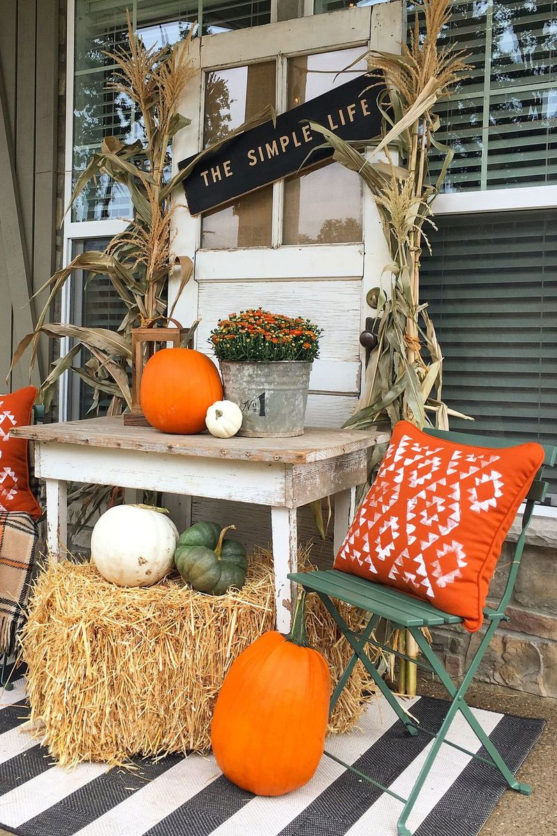 An amazing fall outdoor decoration with corn stalks and hay bales for a fresh fall look