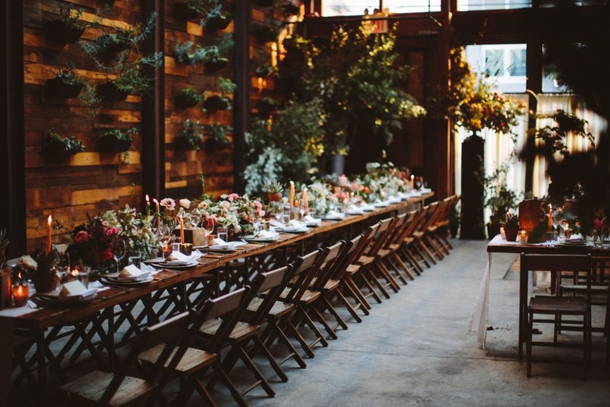 An attractive indoor table set for wedding with long wooden table decorated with colorful flower arrangements, mismatched candles, and eclectic dinnerware.