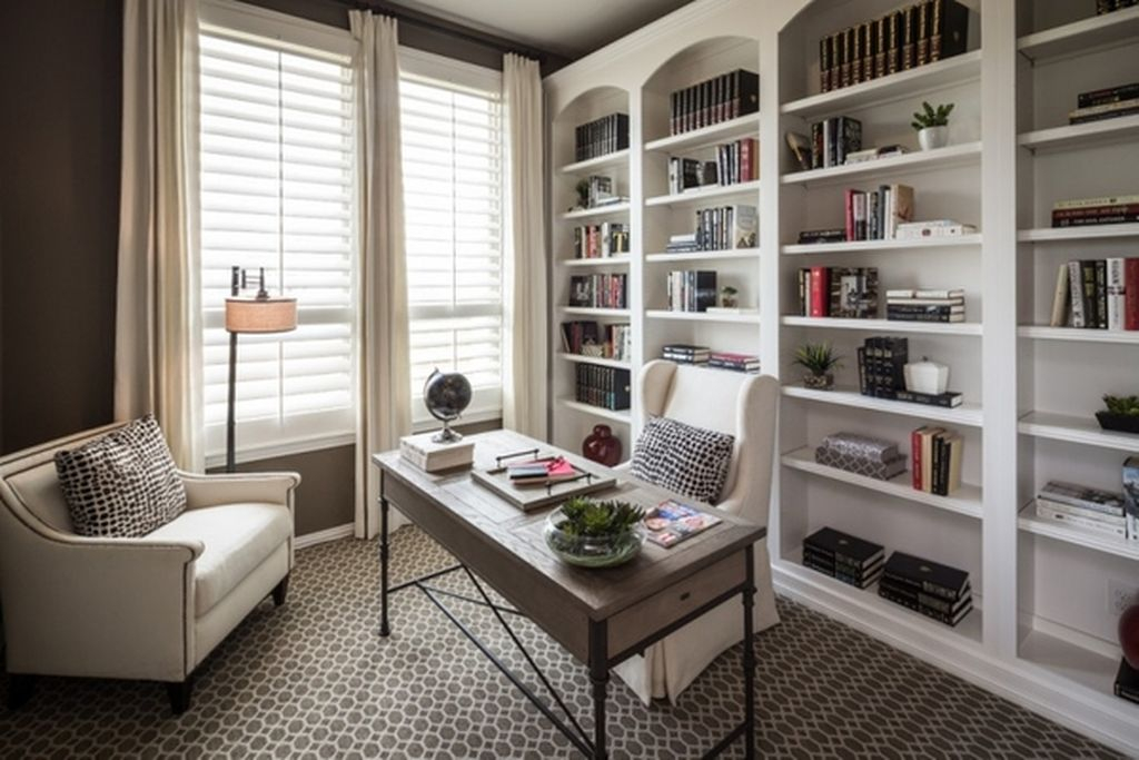 An awesome home office features wall bookshelves painted in white that features four spacious vertical sections which then has a horizontal parting