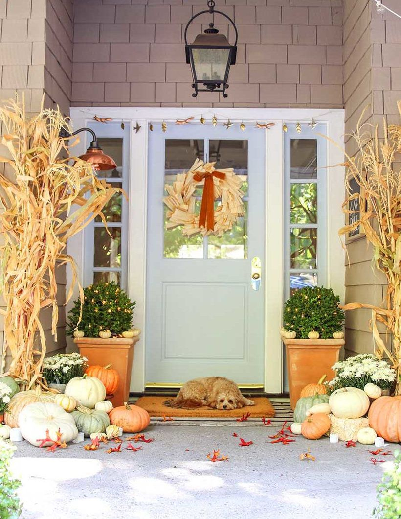 An awesome outdoor redecoration from summer to fall with beautiful matching corn stalks, an array of pastel pumpkins, mini pumpkin and a charming door