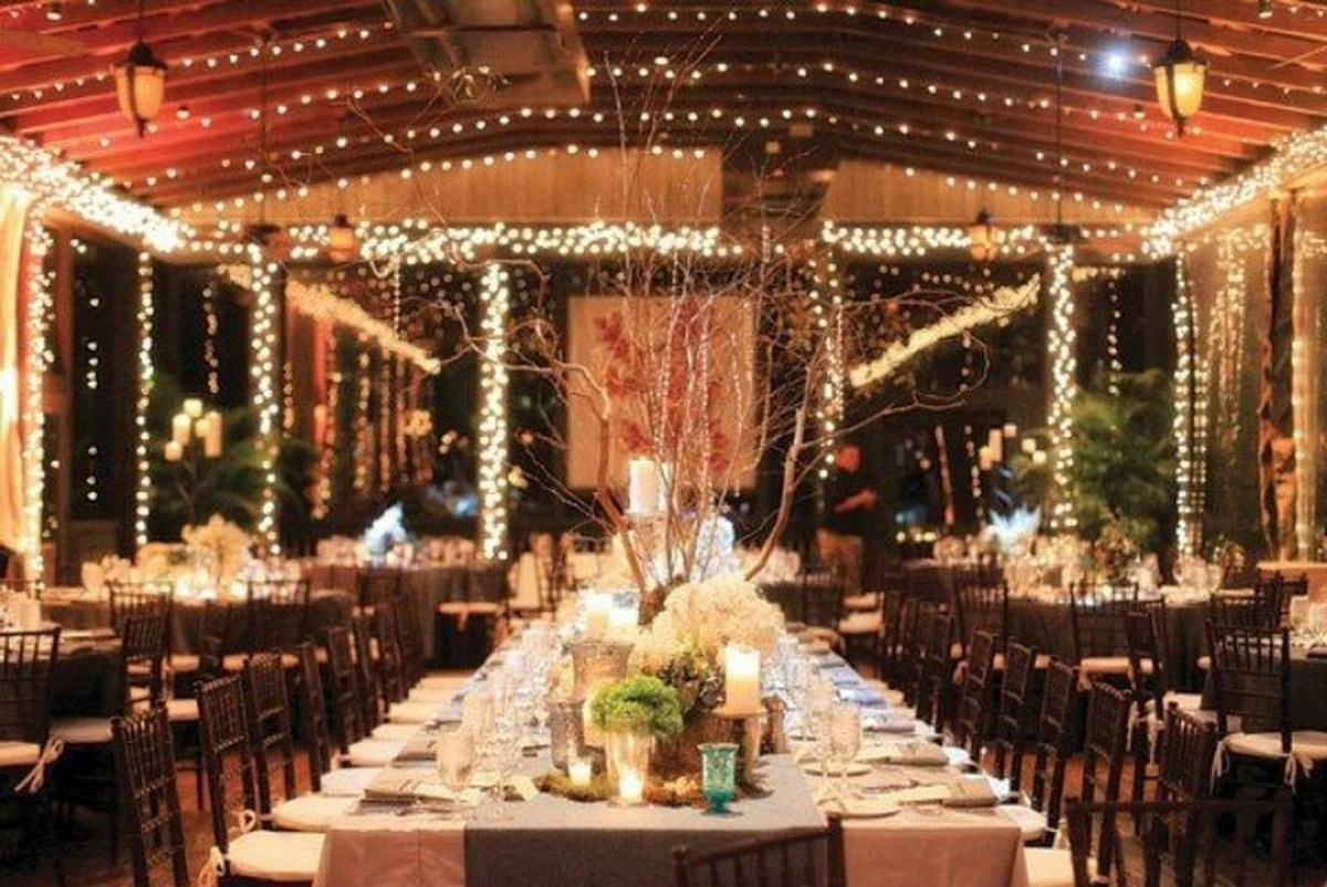 An elegant indoor venue for fall wedding with lighting, shape of tables, style of chairs, and linens and paper lanterns, trees and plants to your wedding room.
