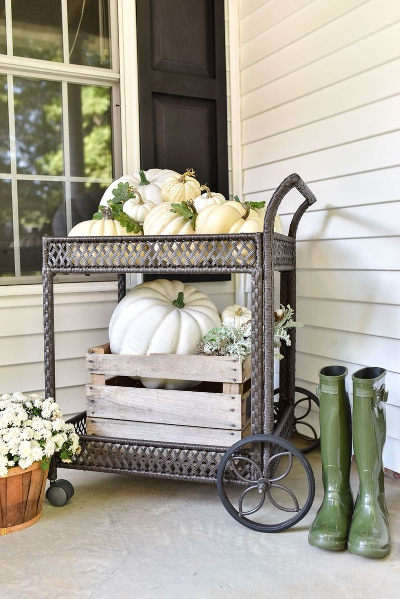 An impressive outdoor redecoration from summer to fall with pumpkins cart and shelf add more flair by interspersing a bit of greenery.