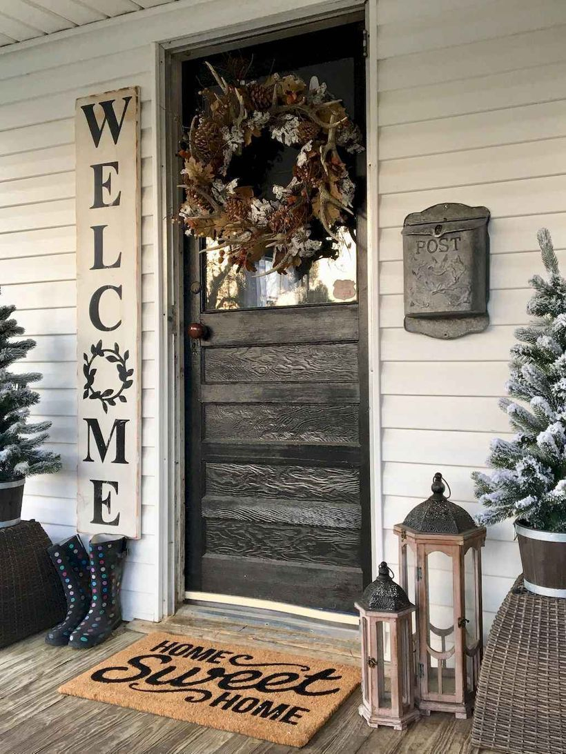 Best farmhouse porch decor ideas with wreath of flowers, twigs, pine fruit, wooden lamps and plants above the basket of rattan