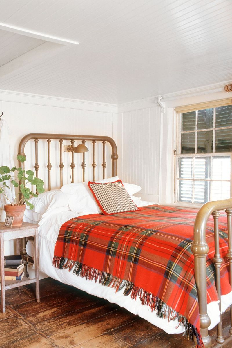 Fall bedroom decoration with a plaid blanket featuring red, orange, and golden hues to decorate this fall decoration