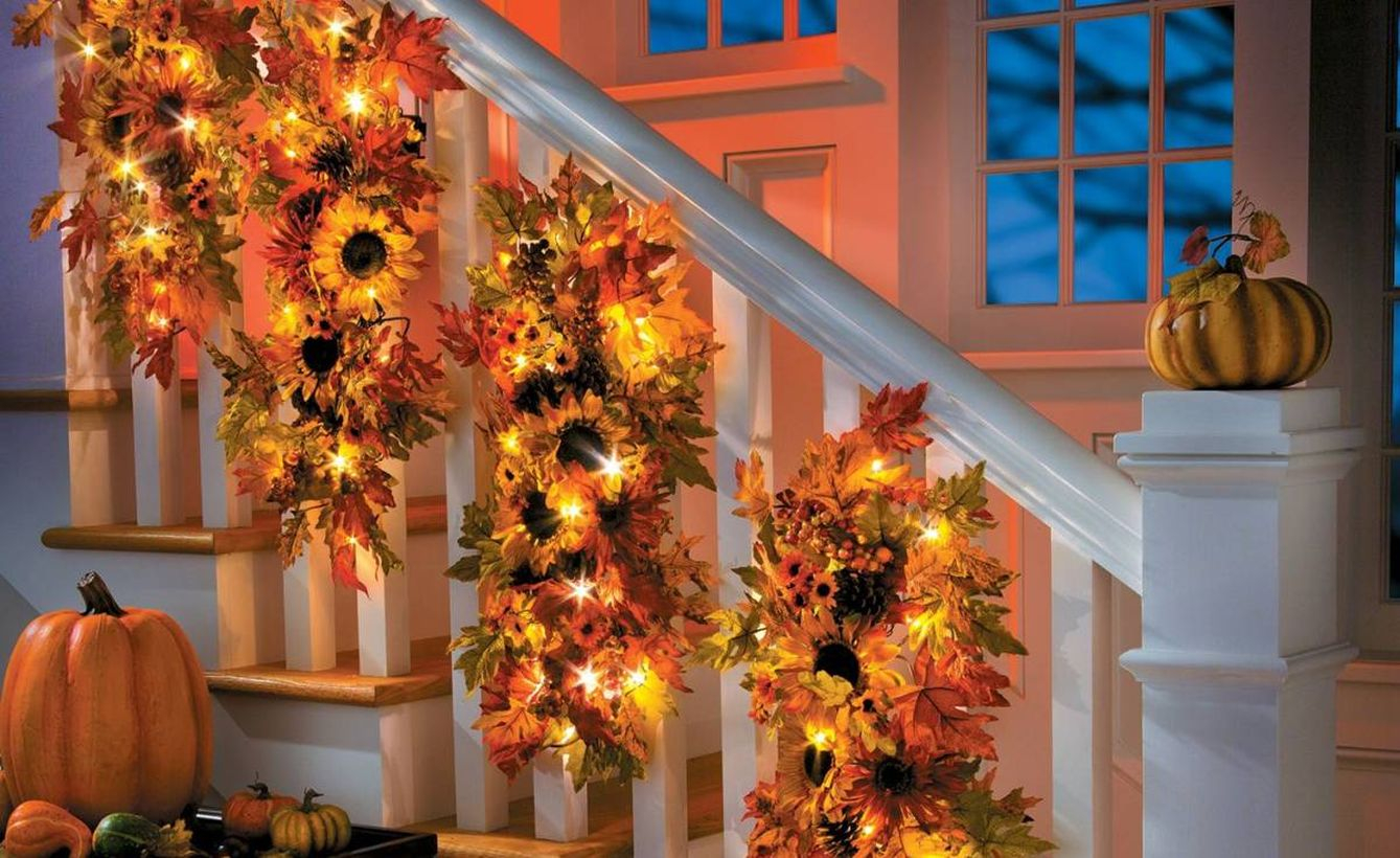 Pretty dry leaves garlands with sunflowers and small lamps to make your stairs good