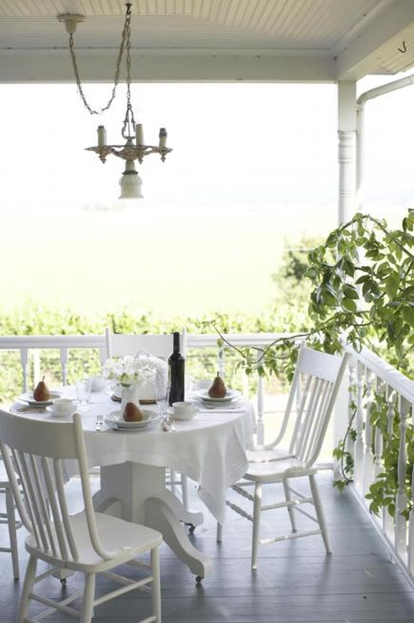 Stunning seating ideas with wooden white chairs, a white round table, white tablecloth and a hanging lamp