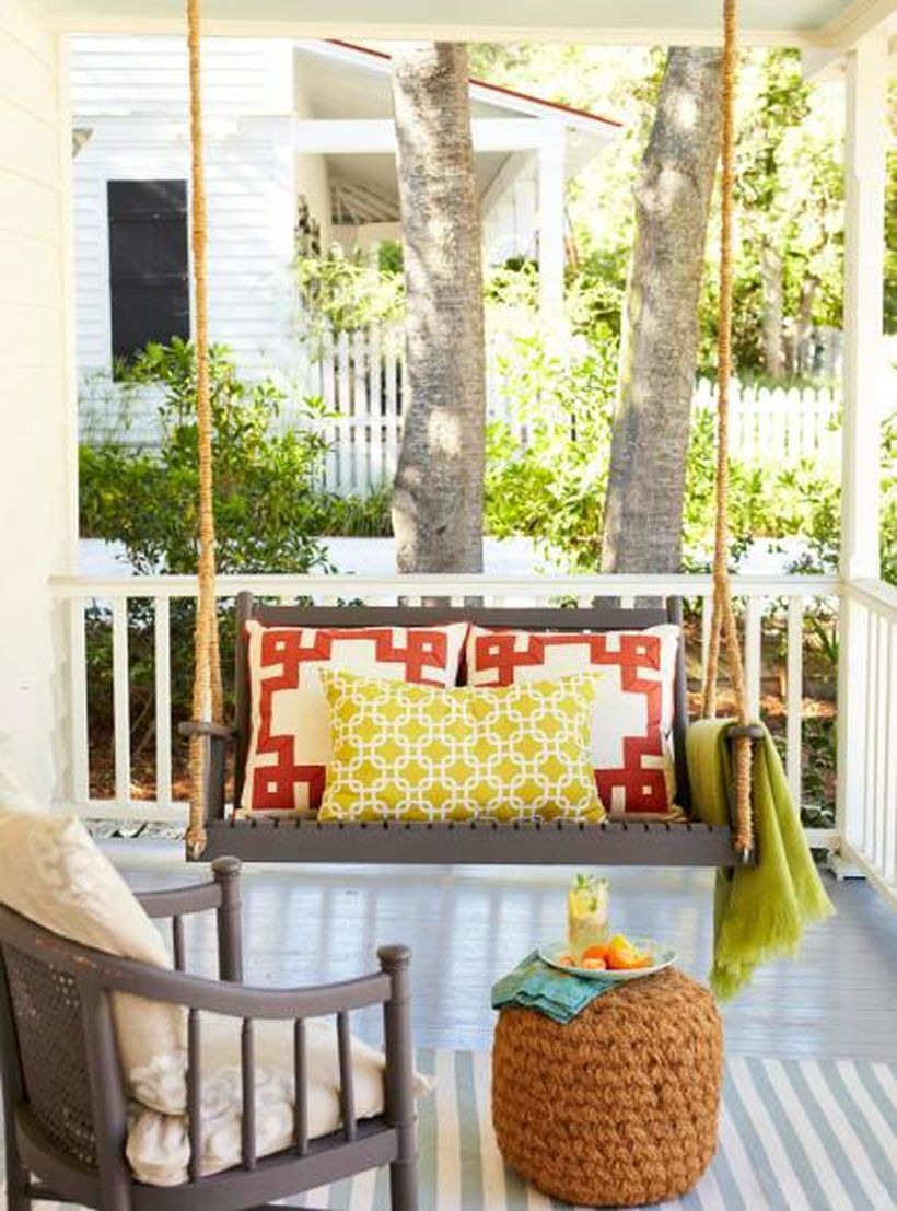 Unique seating ideas with wooden swing chair, red and yellow pillows