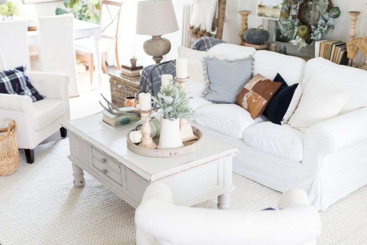 Stunning white living room with white sofas, white rug, and decoration white pumpkin on table coffee you must try