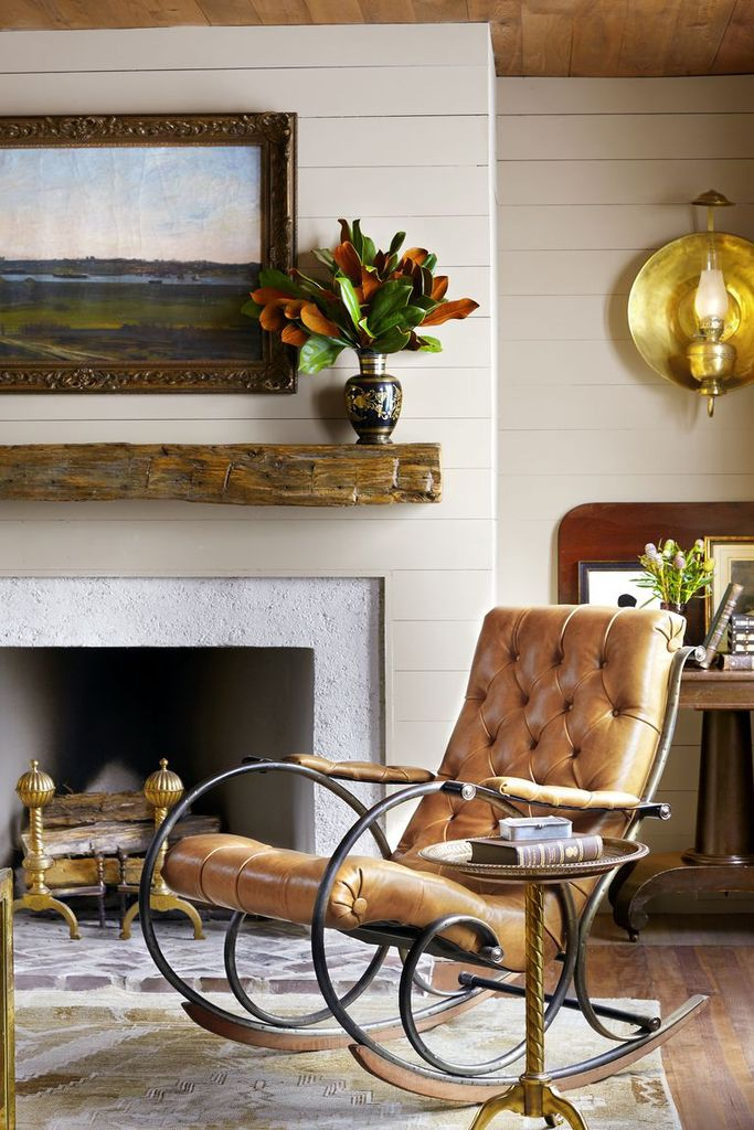 A bunch of magnolia leaves add a fresh note to a neutral living room to perfect in this fall. the branches pick up warm colors of the space, including a reclaimed-wood mantel.