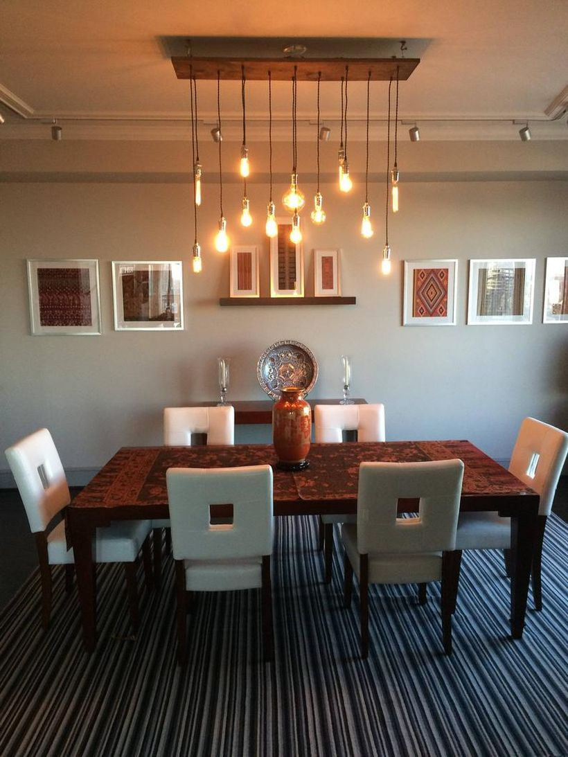 A creative rustic chandelier for dining room with 14 pendant wood chandelier, black table, white chairs, large carpet and decoration on the wall.