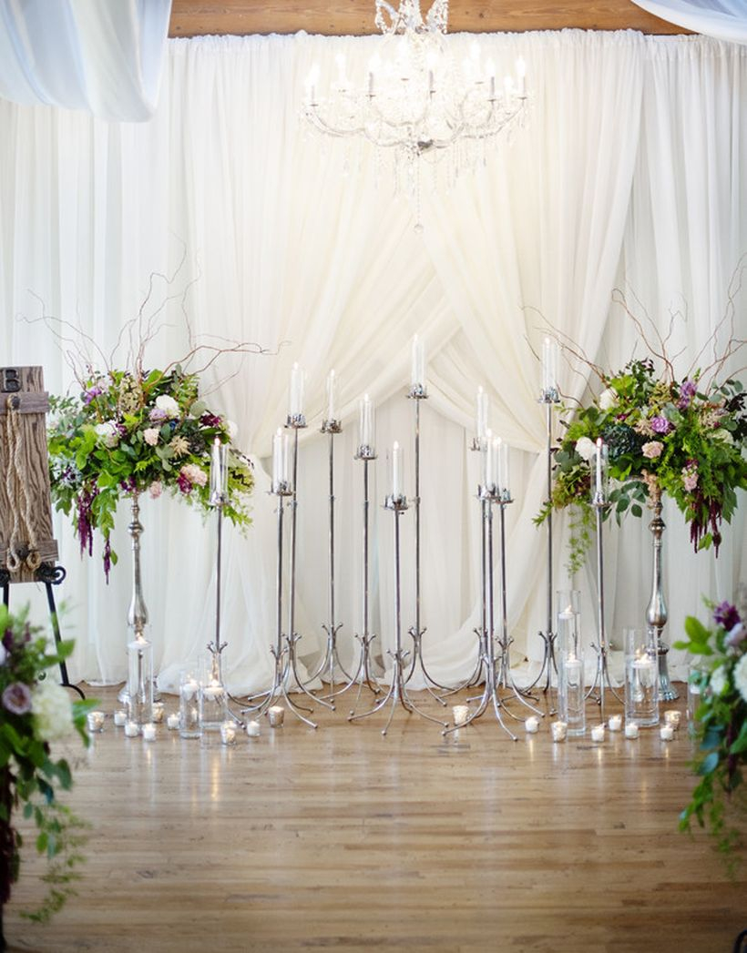 A dramatic backdrop created using floor candelabras, fabric draping and floral arrangements brings a european wedding feel to your ceremony