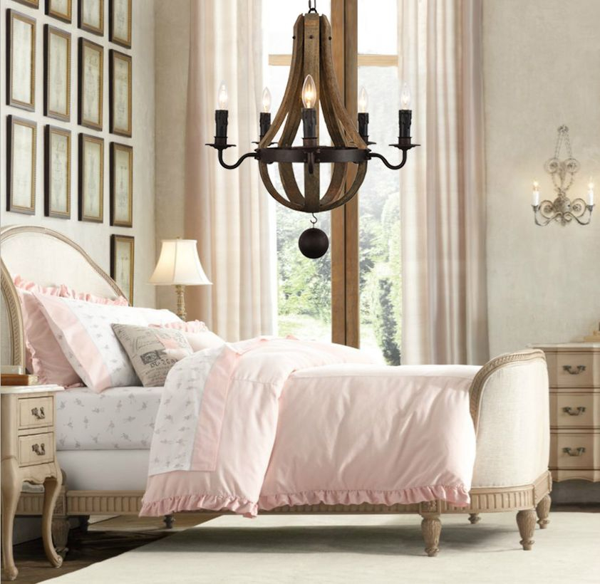 A fabulous rustic chandelier for bedroom with rustic wooden pendant chandelier, thick blanket, large carpet, fireplace, big windows, long white curtain and decoration on the wall.