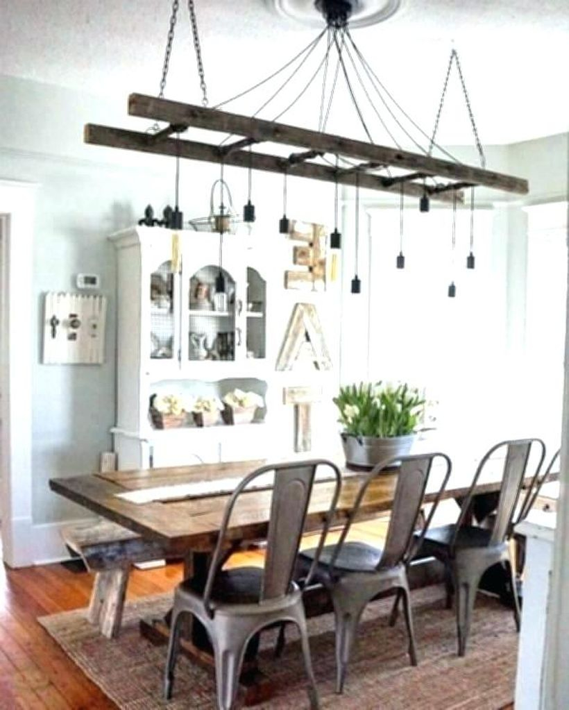 A wonderful rustic chandelier for dining room with track chandelier, big wooden table, iron chairs, white closet, small carpet and large windows.