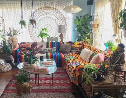 An amazing boho living room with colorful sofa, patterned red carpet, combined with white patterned curtains, green plants in the corner and plants in small pots on rattan tables