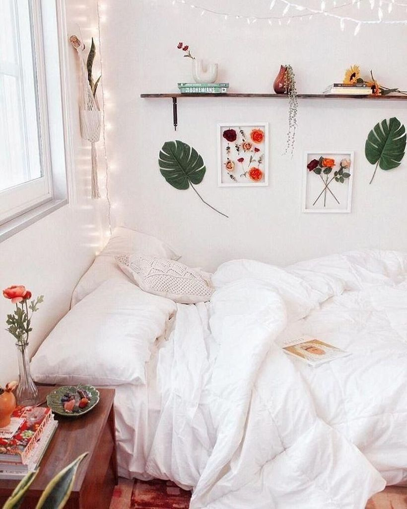 An amazing girls room decoration with white bed, white pillow, white blanket, wooden rack on the wall and hanging string lamps