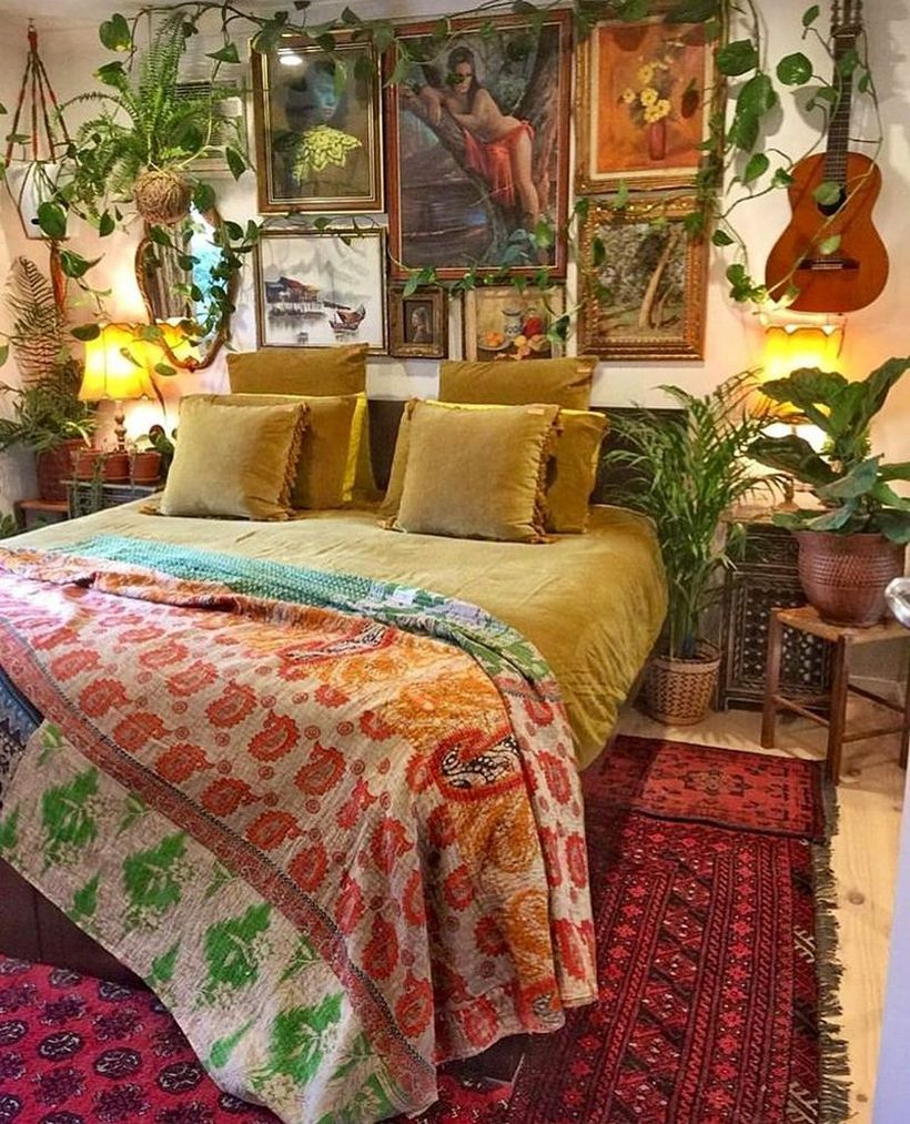 An awesome boho bedroom style with colorful patterned blankets, yellow bed combined with red patterned carpets, wall paintings, and plants as room fresheners