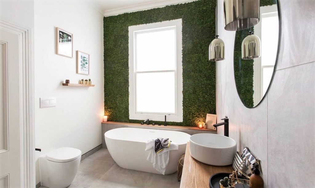 An amazing bathroom design with round mirror and white tub combined with moss near the window to beautify your bathroom design