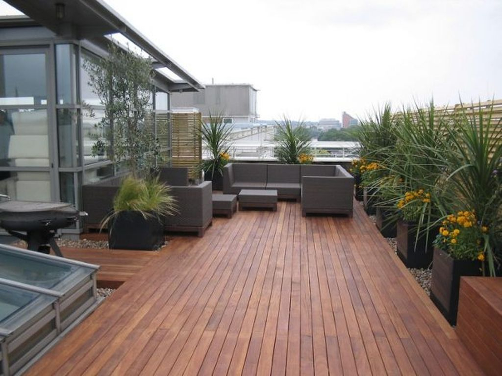 An awesome rooftop design with dark sofa combined with wooden floor and plants around it to perfect your rooftop garden