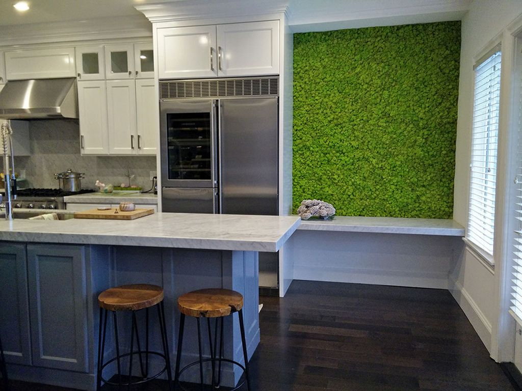 An elegant kitchen design with white cabinets and dark floor combined with moss wall to make impression nature in the kitchen