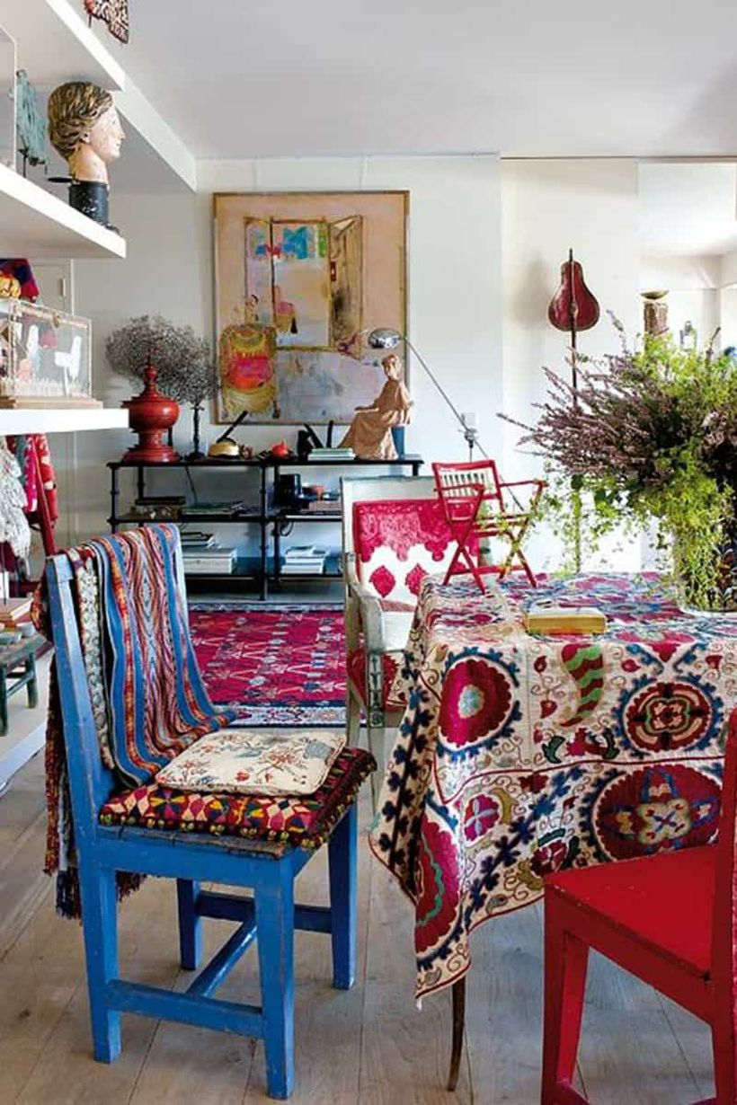 An extraordinary furniture for bohemian home decorating with colorful wooden chair, boho tablecloth, rug boho and tapestries on the walls.