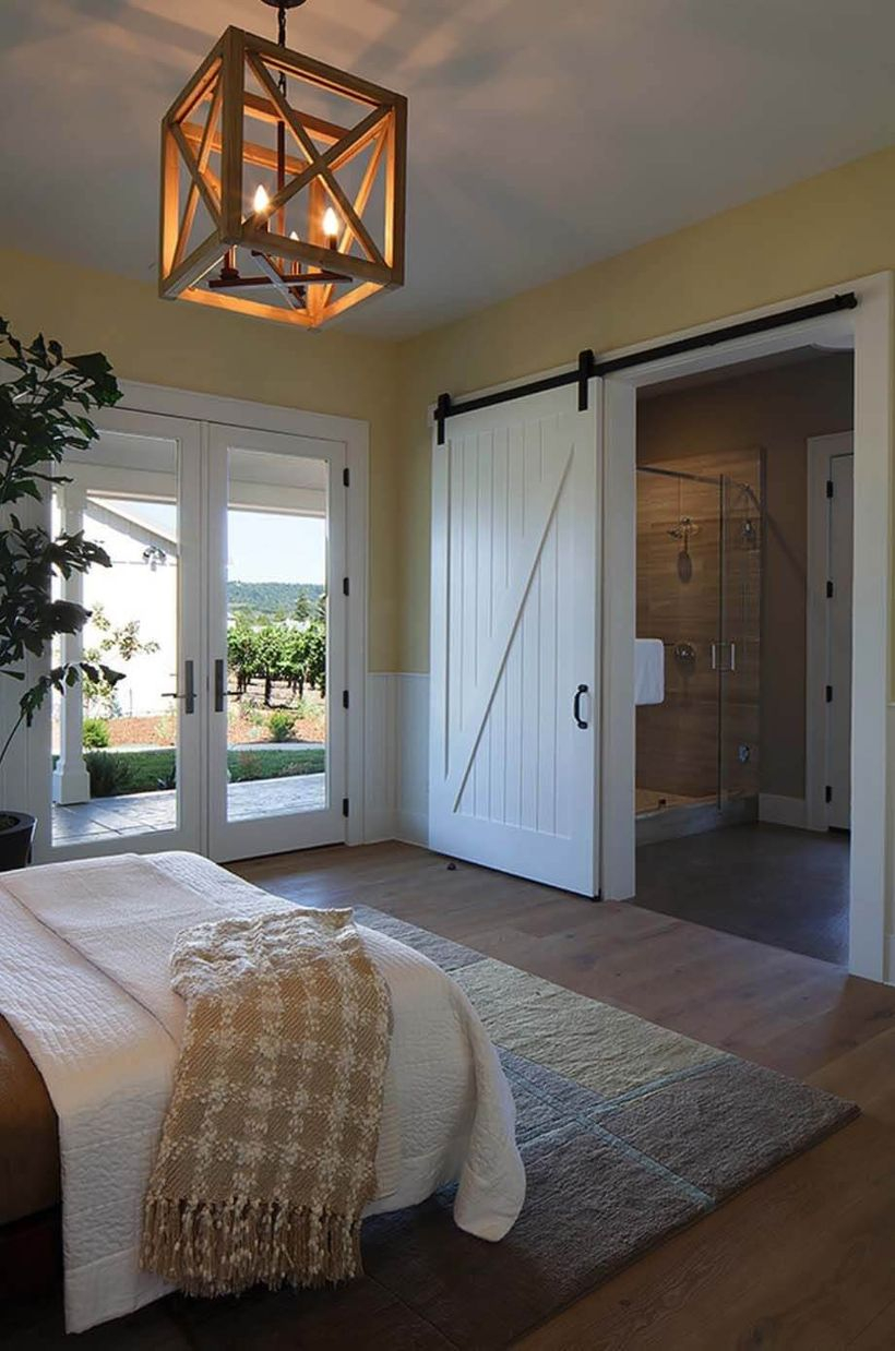 An extraordinary rustic chandelier for bedroom with edison's manor chandelier, sliding wooden door, house plant, large carpet, wooden floor, a white blanket and wooden floor.
