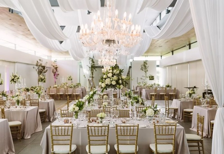 Fancy wedding decoration with bright colored drapes and chandelier ramps up the glamour