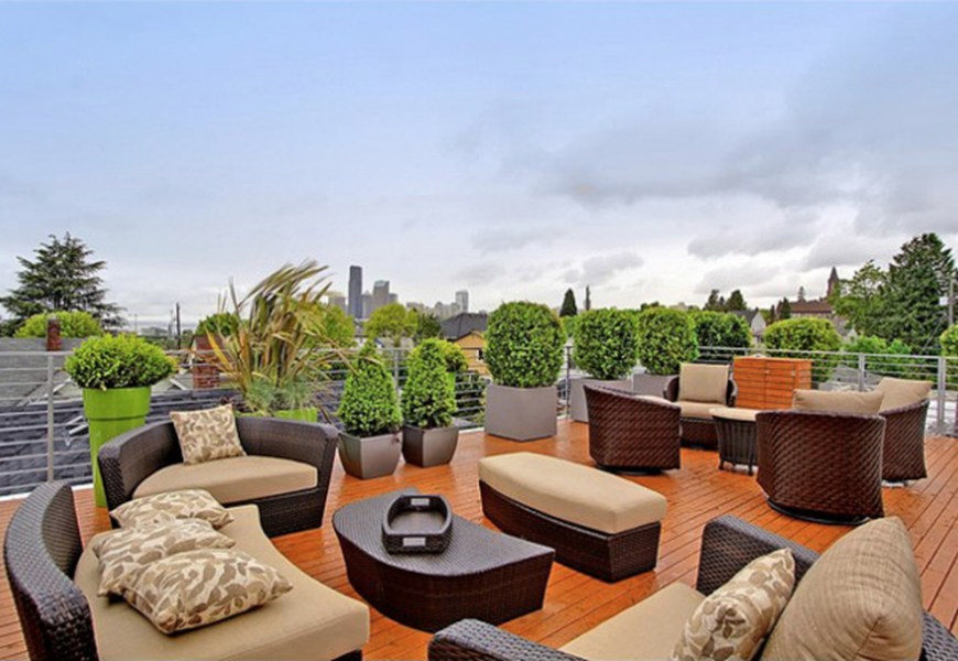 Modern small rooftop design with rattan seating combined with wooden floor and plants around it to perfect your rooftop garden